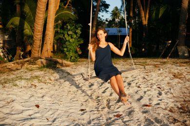 Девушка раскачивается на качелях на берегу