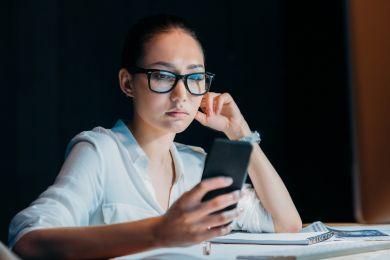 Уставшая девушка смотрит на экран смартфона