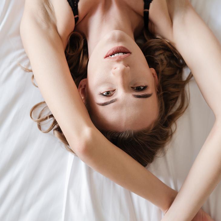 Молодая девушка лежит на кровати
