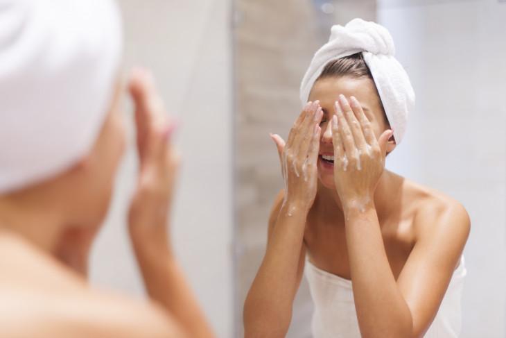 умывание лица девушка очищает кожу