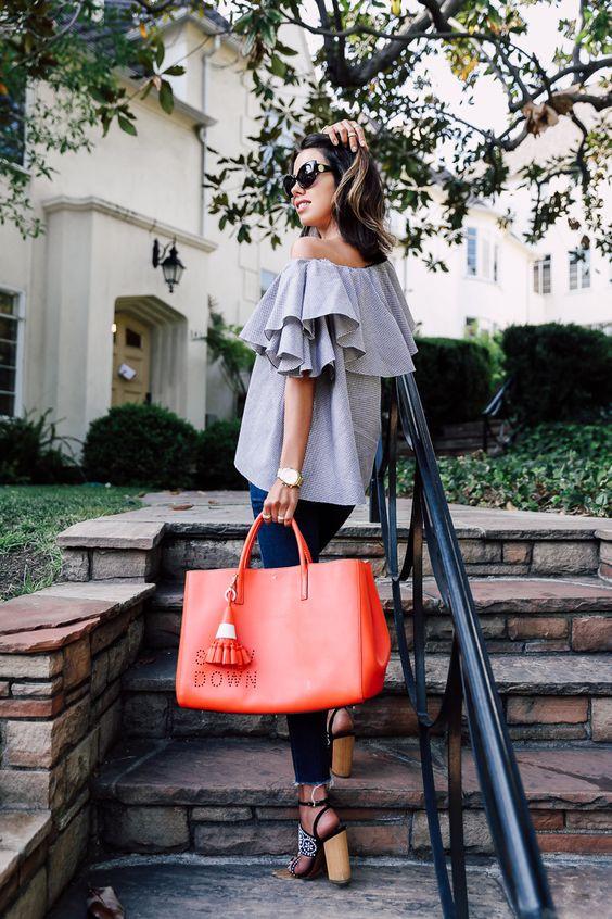 Яркая сумка кораллового цвета в руках у девушки