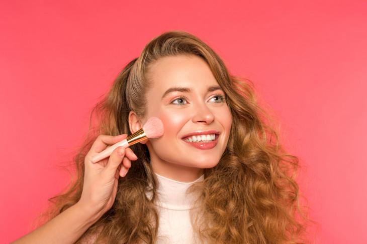 Девушка наносит румяна кистью для макияжа