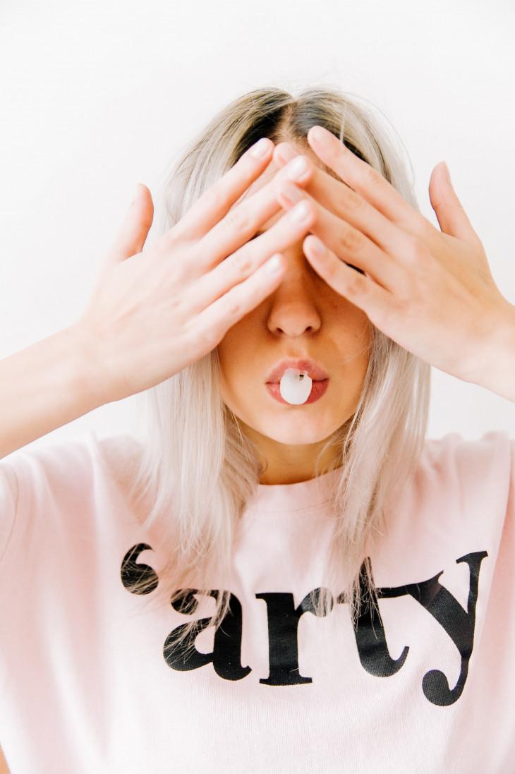 Девушка закрывает лицо руками