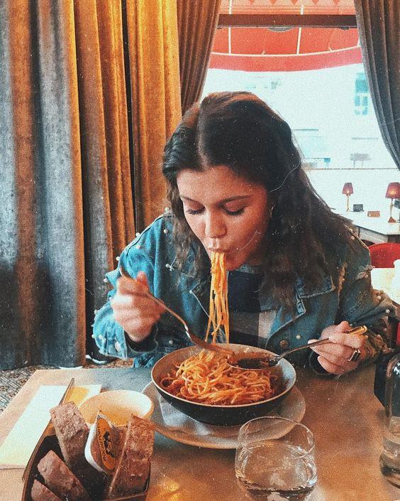 Девушка ест пасту с удовольствием