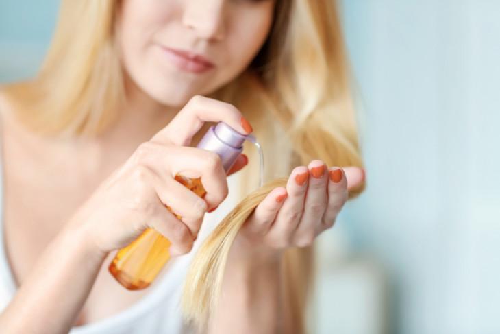 Девушка наносит масло для волос на кончики
