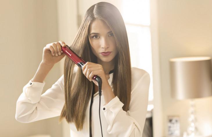 Девушка выпрямляет волосы